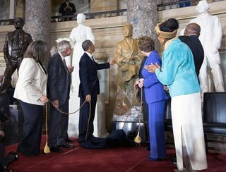President Barack Obama touches the Rosa Parks statue after the unveiling during a ceremony in Statuary Hall at the U.S. Capitol in Washington, D.C., Feb. 27, 2013.